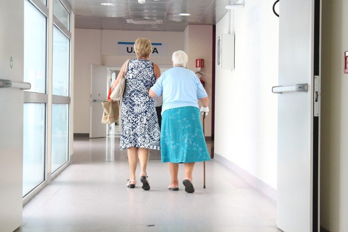 尿失禁のため病院のトイレでオムツパッドの交換に向かう高齢者と家族