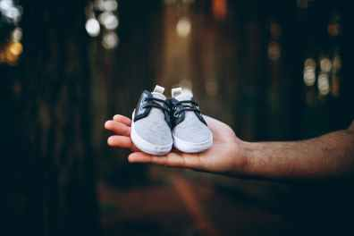 tiny sneakers on hand of man in nature