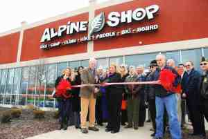 """Owners Russell """"Holly"""" (fifth from left) and Lisa Hollenbeck cut the ribbon at Alpine Shop O'Fallon's Grand Opening celebration on Friday, March 22."""