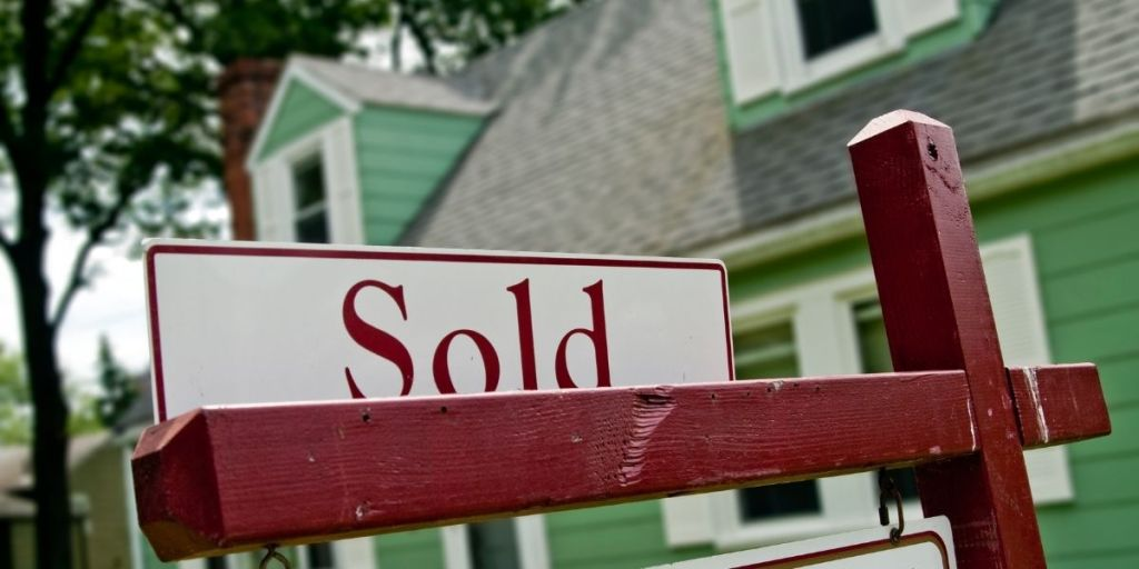 """A sign reading """"sold"""" in front of a green house surrounded by trees."""