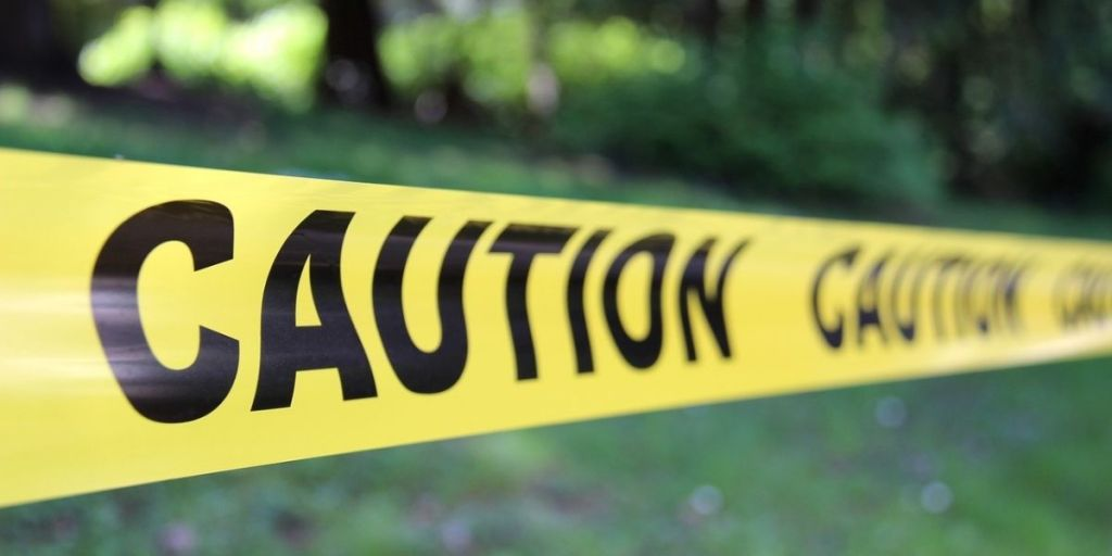 Yellow caution tape with CAUTION in black letters in front of a yard with trees