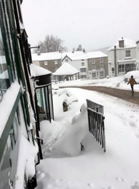 View of snowy street from shop