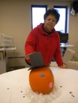 Melvina adjusts a pilgrim hat