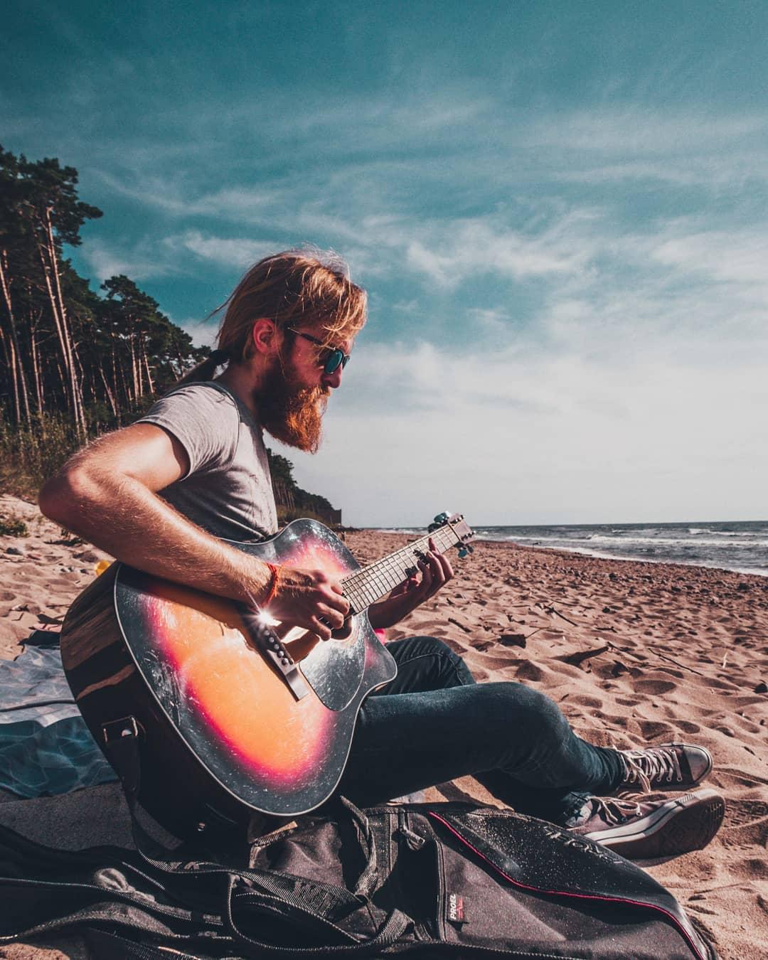 Eduard Banulescu playing guitar on the beach