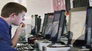 Joven frente a computadora en cibercafé o sala de conexión pública a internet