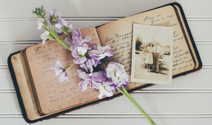 an old opened diary with flowers and a photo