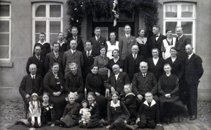 -232- Gesellschaft vor dem Haus Ostendorf, später Wehry. Das Haus brannte ab und wurde neu aufgebaut. In der Mitte Ehepaar Maria und Ornd Ostendorf.