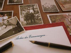 """Symbolbild: alte schwarz-weiß-Familienfotos, ein alter Füller und die Aufschrift """"Archiv der Erinnerungen"""""""