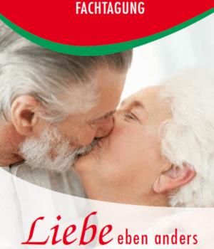 Das Bild zeigt ein sich küssendes Paar (Mann und Frau). Beide haben graue Haare.