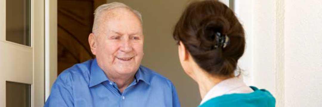 Titelbild des Beitrags. Zu sehen sind ein Senior und eine Frau, beide begrüßen sich und lächeln sich an.