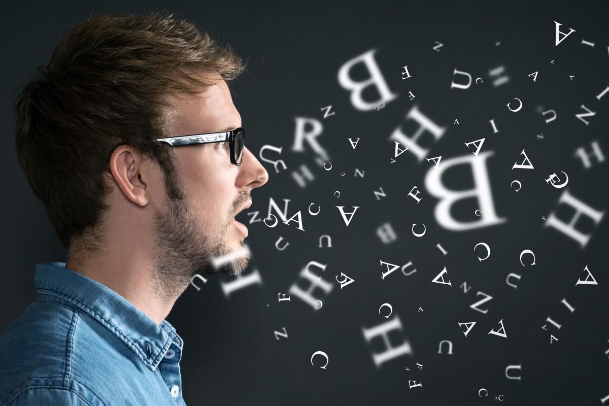 Eine Person spricht und aus ihrem Mund fliegen Buchstaben.