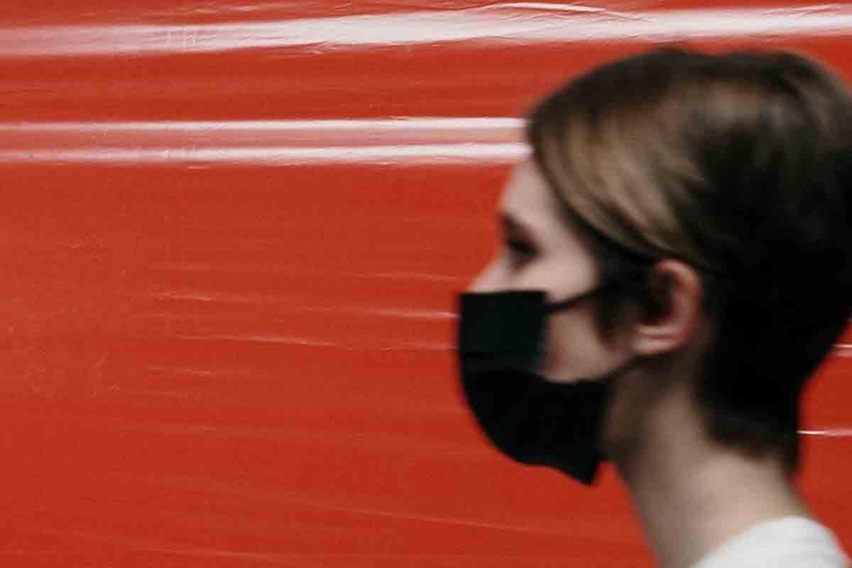 Eine Frau trägt einen schwarzen Mundschutz.