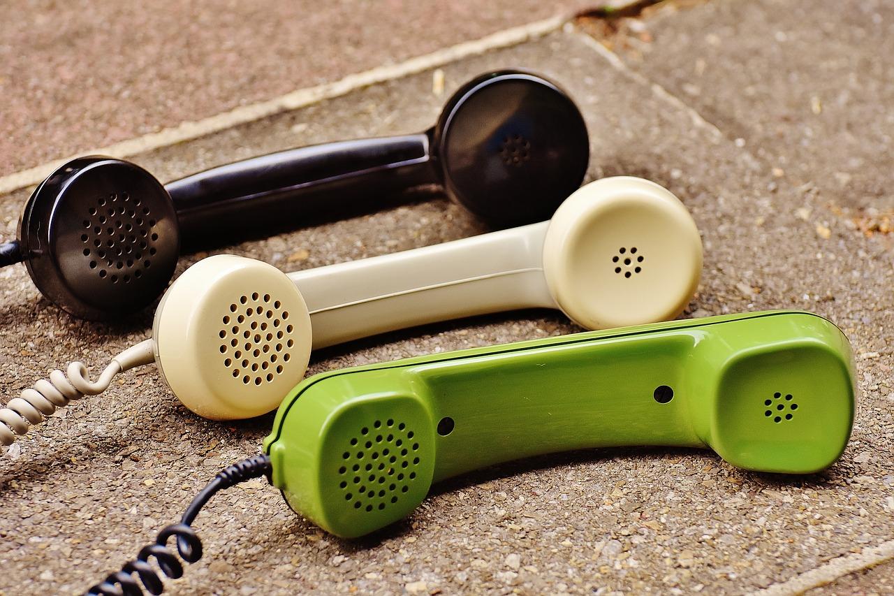 Drei Telefonhörer liegen auf Steinplatten
