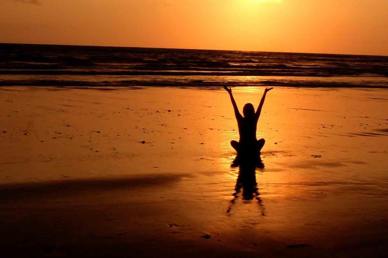 Eine Person macht Yoga am Strand mit dem Blick in Richtung Sonnenuntergang.