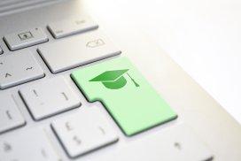 Fotoausschnitt einer grauen Computertastatur mit grüner Entertaste. Auf der Entertaste ist ein Absolventenhut abgebildet