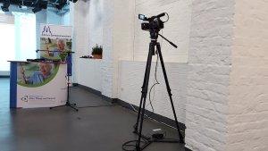 Kamera ausgerichtet auf Counter und RollUp der 8. Kölner Demenzwochen