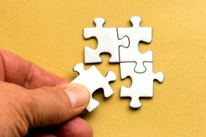 Eine Hand fügt ein Puzzleteil zu einem Puzzle hinzu.