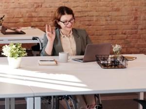 Eine Frau, die in einem Rollstuhl sitzt, nimmt über ihren Laptop an einem Meeting teil.