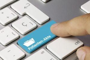 Ein Finger betätigt eine Taste auf einer Tastatur. Das Bild wurde so bearbeitet, dass auf der Taste Patienten-Akte steht.