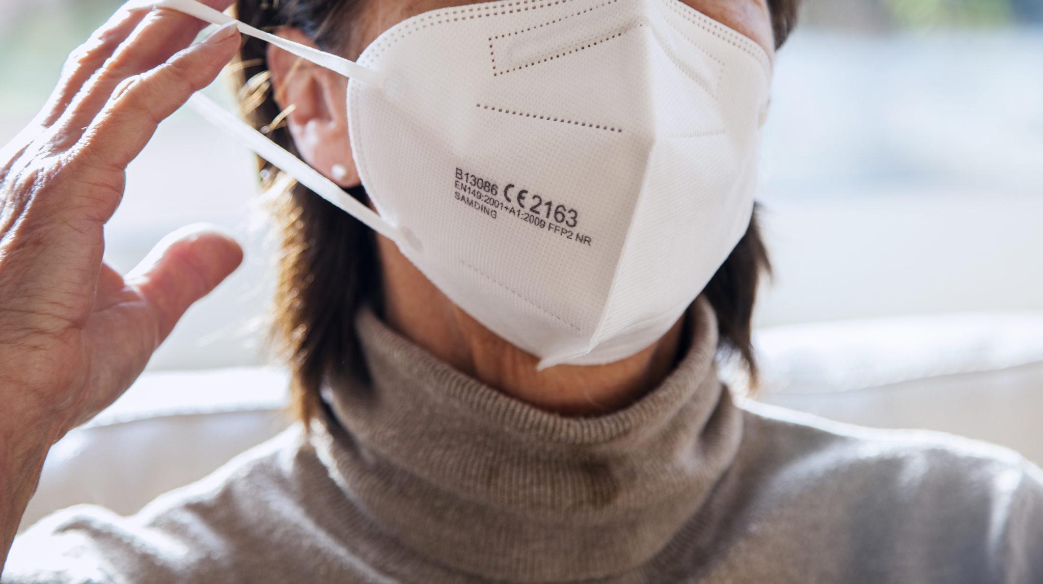Nahaufnahme einer Frau, die eine FFP2-Maske anzieht.