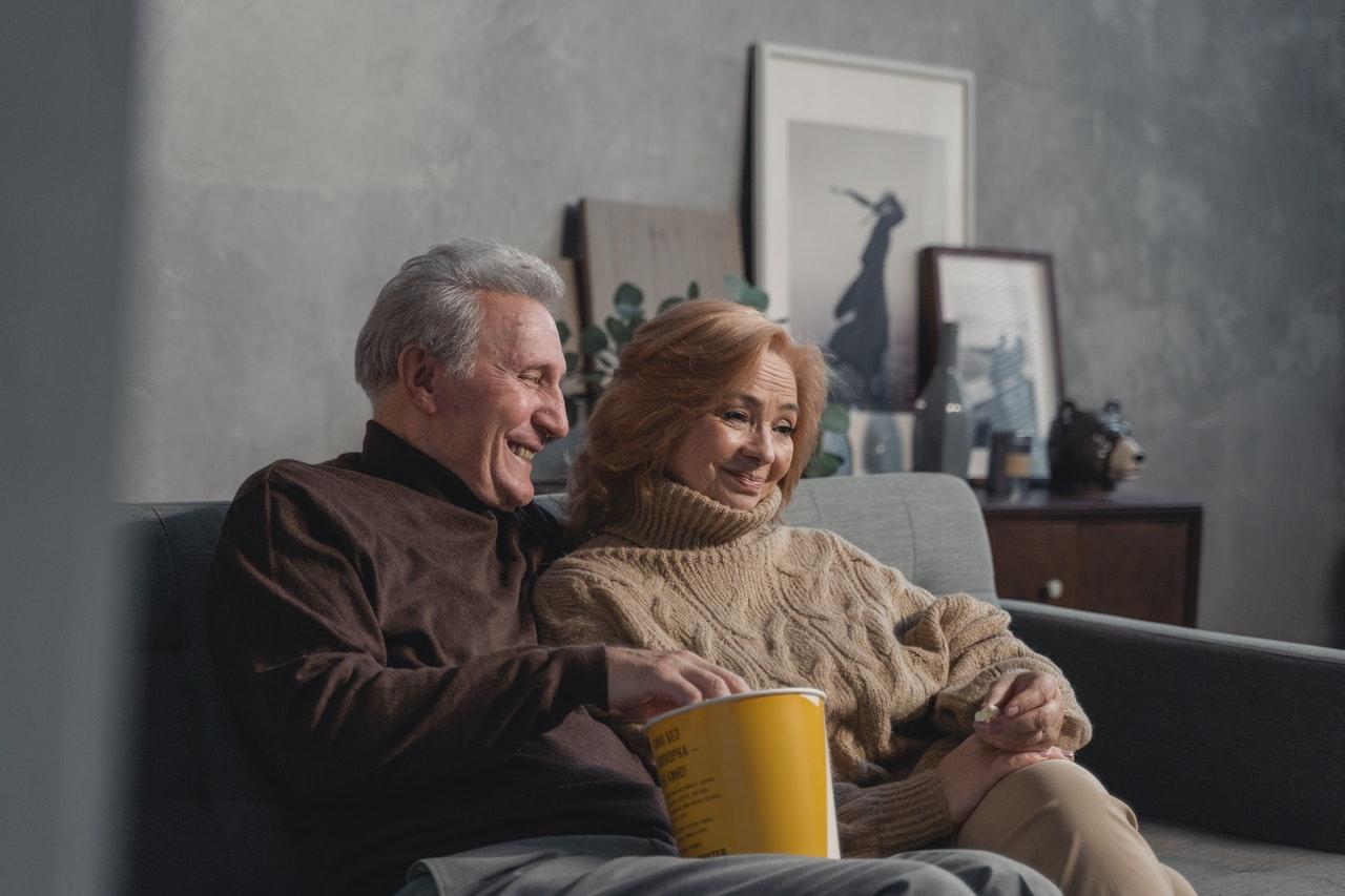 Zwei Senior*innen sitzen auf einer Couch und essen Popcorn. Sie schauen einen FIlm.