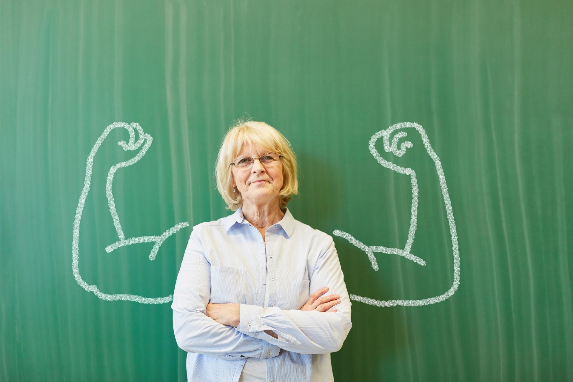 Eine Frau steht vor einer Tafel. Rechts und links von ihr wurde ein starker Arm auf die Tafel gemalt. Dies steht für Resilienz.