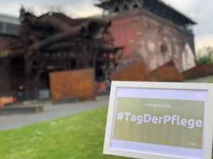 """Foto der Jahrhunderthalle Bochum, im Vordergrund ein Bilderrahmen mit dem Text """"Internationaler Tag der Pflege"""""""