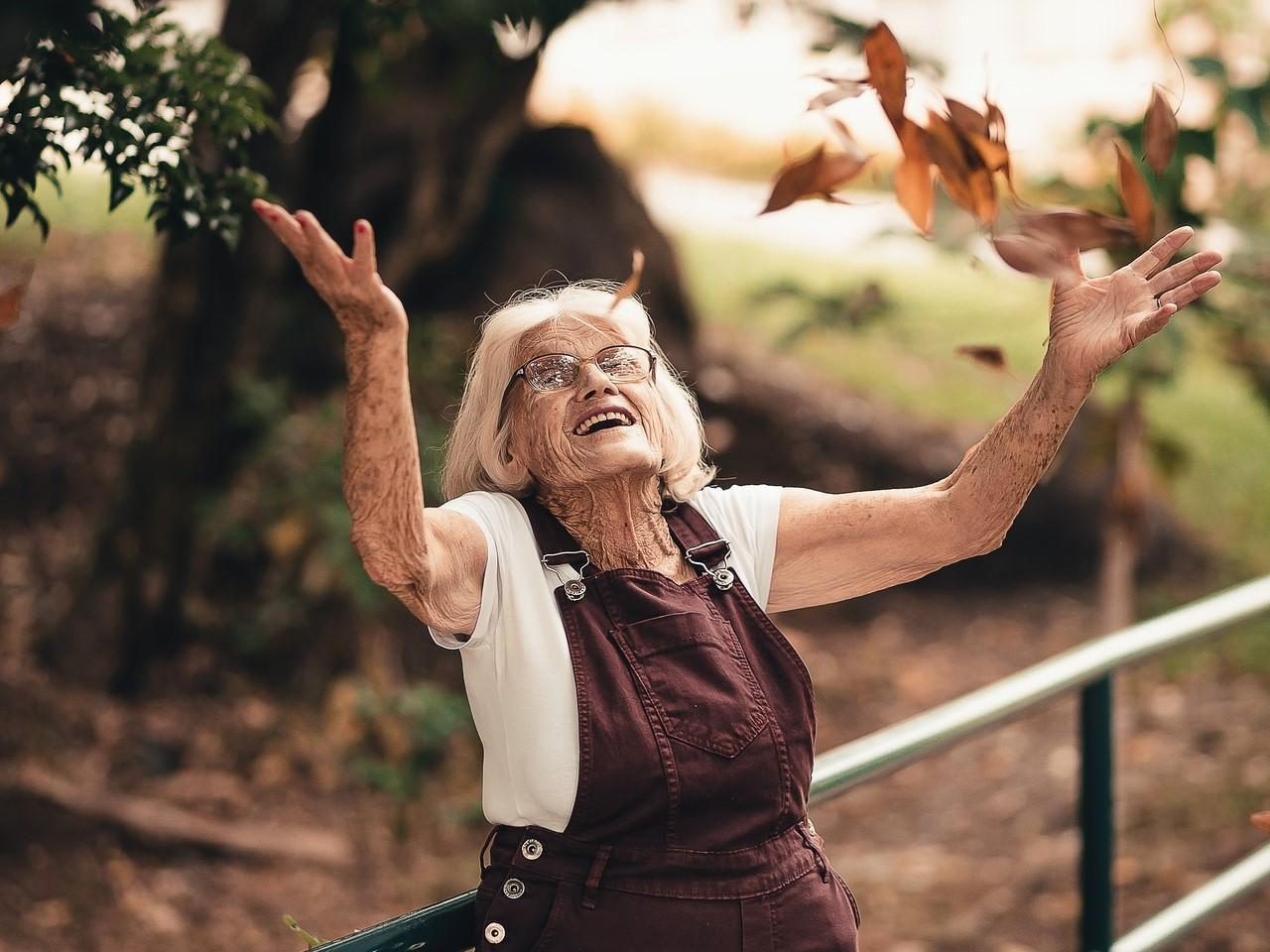 Eine Seniorin wirft glücklich Blätter in die Luft.