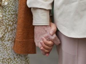Zwei Senior*innen halten ihre Hände fest.