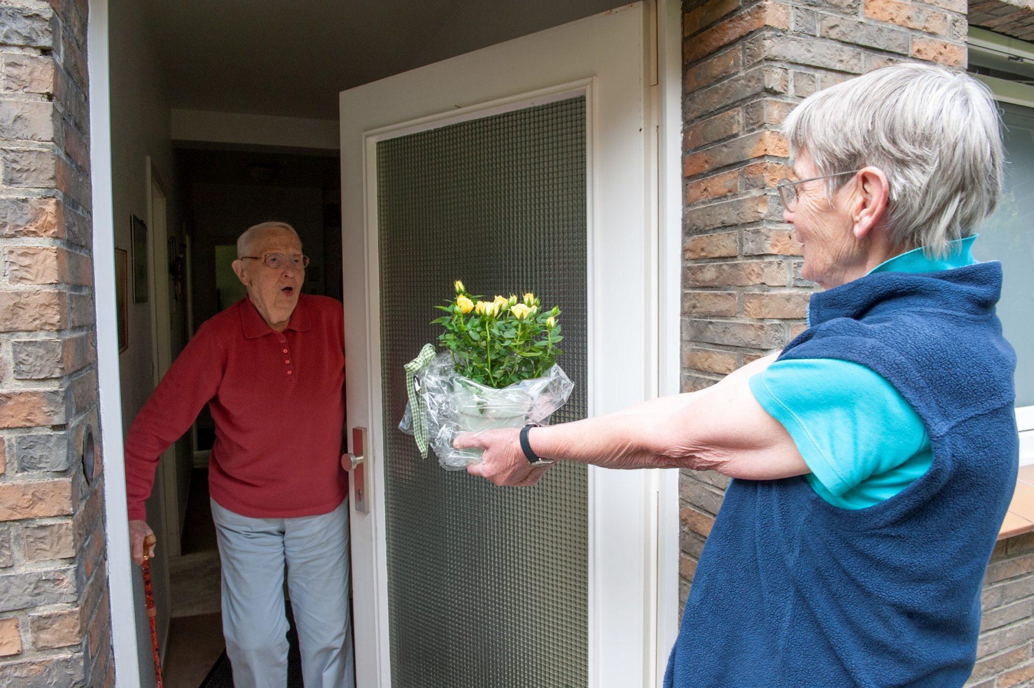 Einem Pflegenden Angehörigen werden Blumen überreicht.