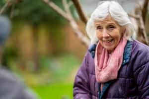 Eine Seniorin ist im Garten und lächtelt in die Kamera.