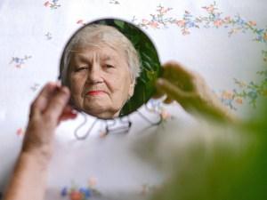 Eine Seniorin betrachtet ihr eigenes Spiegelbild in einem kleinen, runden Spiegel.
