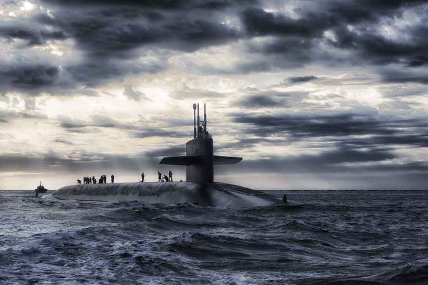 grey submarine in body of water under cloudy sky