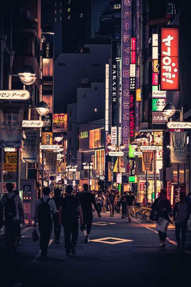 people walking on the street between buildings