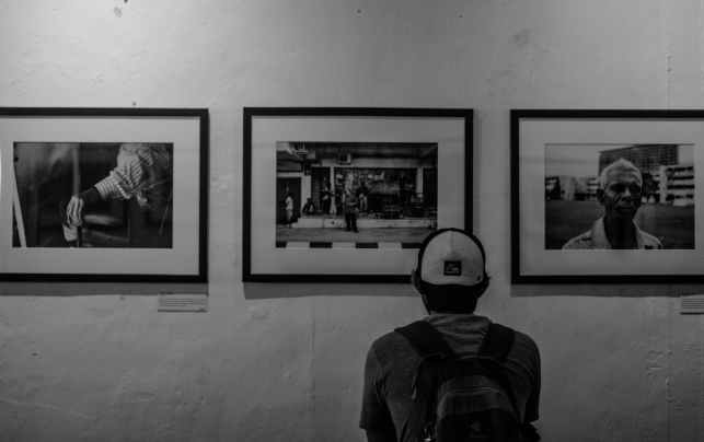 grayscale photo of man wearing white cap in front of three paintings