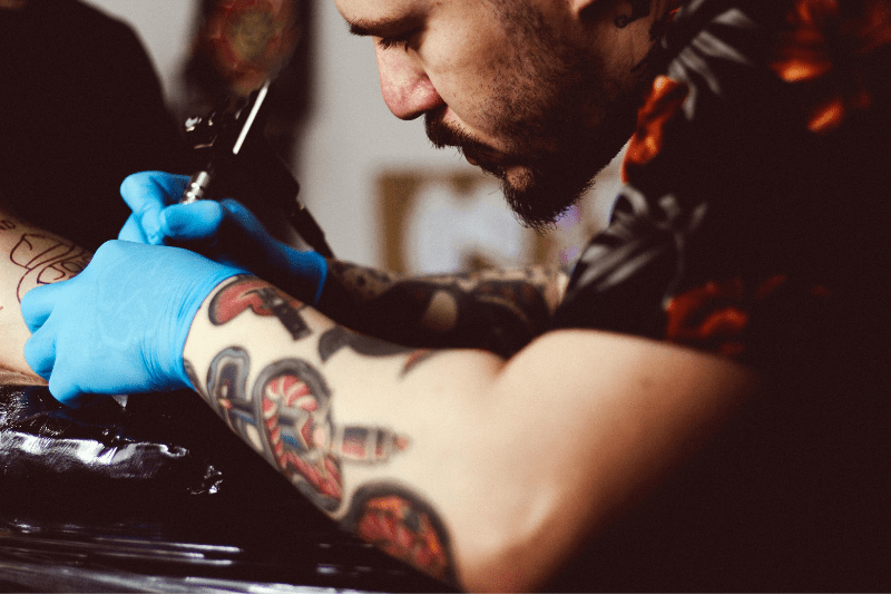 3b59f5ede male tattoo artist working on creating a new tattoo, with the tattoo gun in  hand