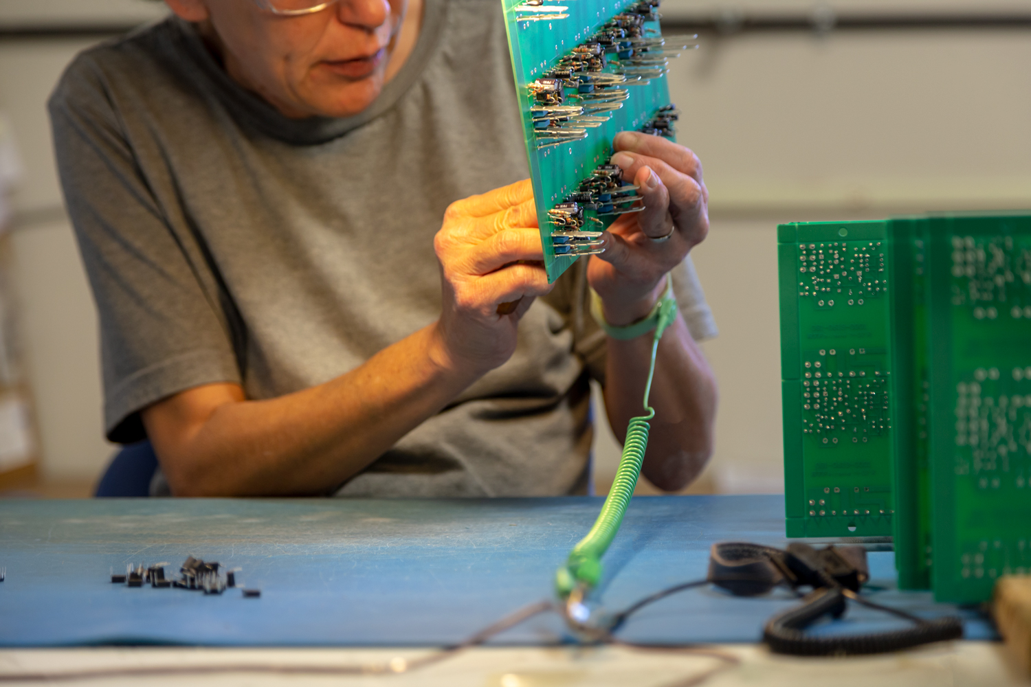 A worker carefully assembles a circuit board While wearing a grounding bracelet .