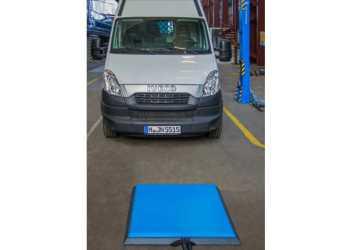Varebilen lades automatisk op, når den køres hen over den blå plade. Foto: Intis
