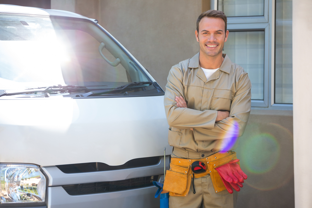 Handyman with tool belt around waist standing next to delivery van