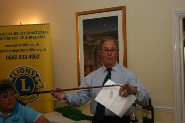 Len Mills as Auctioneer