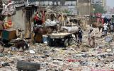 """People walk through Eshash el-Sudan slum in the Dokki neighbourhood of Giza, south of Cairo, Egypt September 2, 2015. Residents of the slum clashed with police in late August, when about 50 ramshackle huts were destroyed and at least 20 people were injured by teargas, local media reported, as authorities attempt to clear the area and rehouse residents. The slum dwellers, some of whom have called Eshash el-Sudan home for 50 years, say there are not enough apartments built nearby to house them. The residents of the slum eke out a living by disposing of rubbish or baking bread. Schooling is too expensive for most of their children, who play with salvaged rubbish amid shacks made out of discarded wood and leather. REUTERS/Amr Abdallah Dalsh TPX IMAGES OF THE DAY SEARCH """"ESHASH EL-SUDAN"""" FOR ALL PICTURES"""
