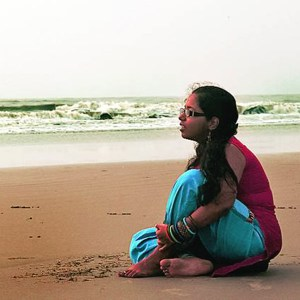 Indian woman sits on beach.