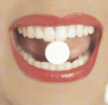 woman with birth control pill between her teeth