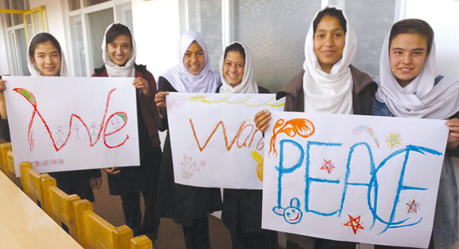 """Students hold up hand-made signs reading """"We want peace."""""""