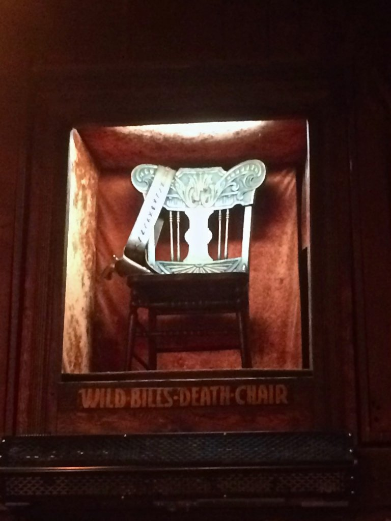 Wild Bill's death chair in Old Style Saloon #10 in Deadwood South Dakota. The chair is illuminated in light above a doorway, with a placard below.