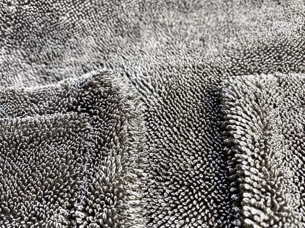 A close up of a gray microfiber towel showing the long loops of microfiber and the edgeless design.
