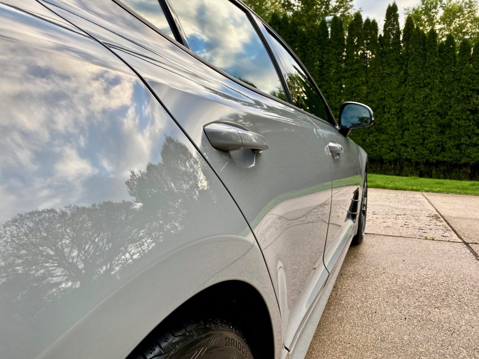 The side of a spotless and shiny gray car, in front of some trees.