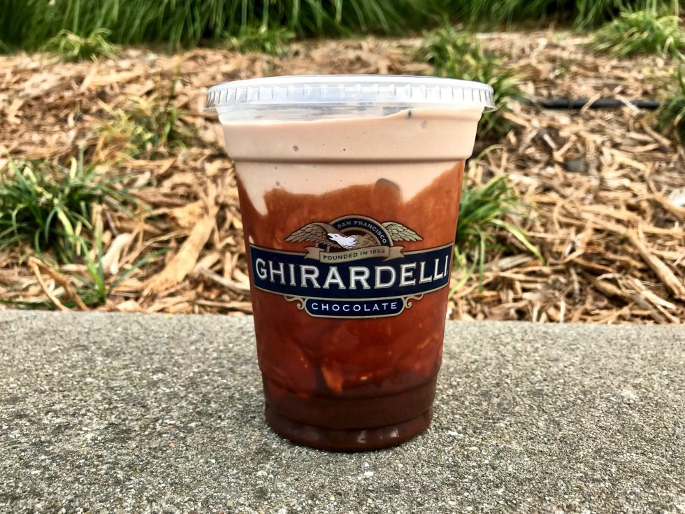 A Ghirardelli chocolate shake sitting on a concrete ledge with plants in the background.