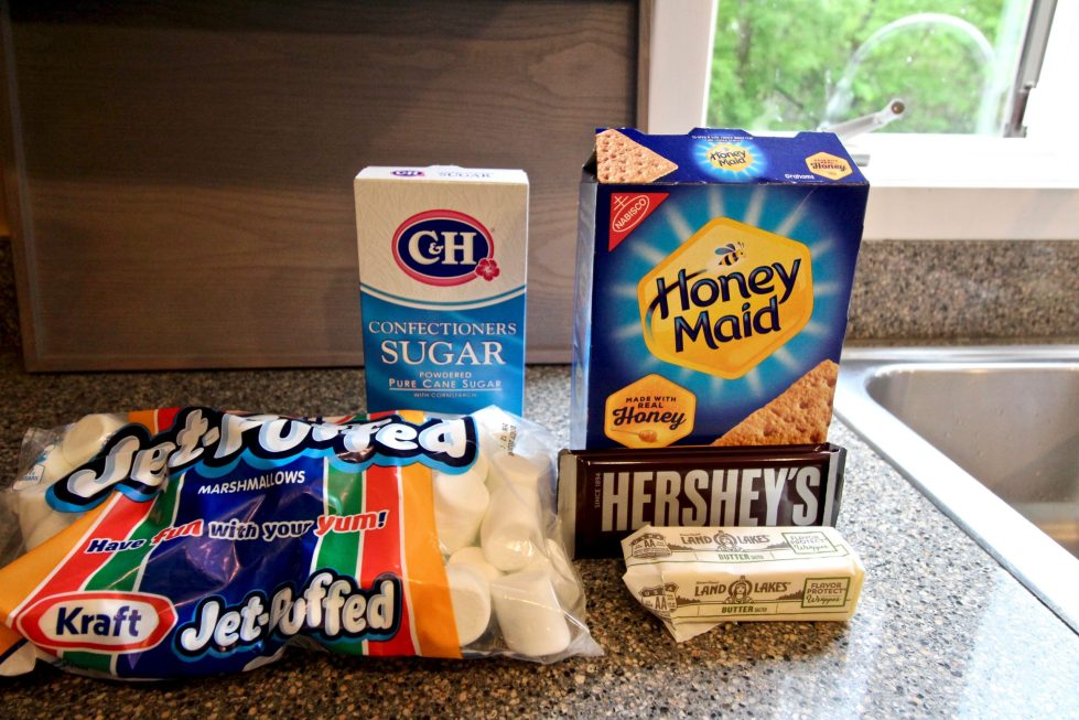 A set of ingredients sitting in their containers on a counter, including graham crackers, marshmallows, sugar, chocolate and butter.