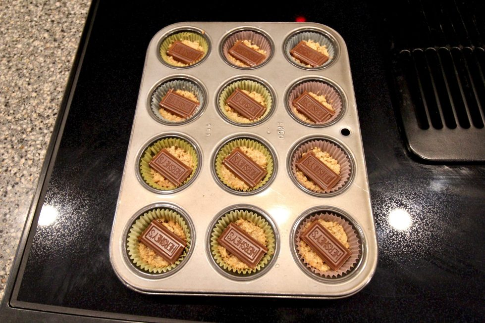 A muffin tray filled with crushed graham crackers and chocolate.